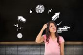 Pretty brunette thinking against chalkboard on grey grid wall