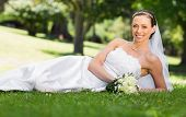 Portrait of beautiful bride with bouquet lying on grass in park