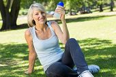 Portrait of happy relaxed woman holding water bottle in the park