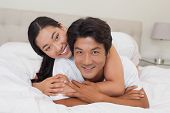 Happy couple lying on bed together at home in bedroom