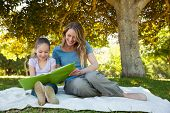 Full length of a happy mother and daughter reading a book at the park