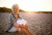 Retired Woman Sitting On The Beach
