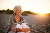 Smiling Old Woman Sitting On The Beach