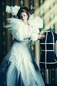 Beautiful fashion model in the refined white dress and mannequin. Vintage style. Art project. Haute