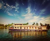 Vintage retro hipster style travel image of travel tourism Kerala background - houseboat on Kerala b