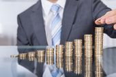 stock photo of coin bank  - Businessman Put Coin To Highest Stack Of Coins