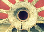 pic of wagon wheel  - Antique rustic wagon wheel center on a barn red background - JPG