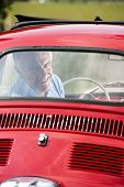 Happy senior man in a vintage car