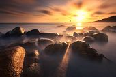 The beautiful sunset with a golden rock