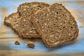 slices of organic, whole grain, dark rye bread on painted wooden cutting board