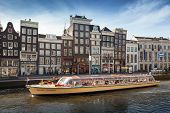 Sightseeing boat goes through the canal in historical center of Amsterdam