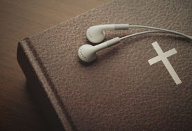 stock photo of godly  - Holy Bible with a resting pair of earbuds over it - JPG