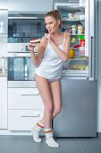 Naughty young woman stealing cake from the fridge making a shushing gesture as she asks for secrecy to hide her guilt