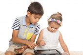 Brother teaches younger sister play on a Tablet PC. Isolated on white.
