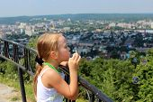 little girl blowing soap big bubbles over the city