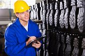 gum boots worker counting stocks and making notes in warehouse