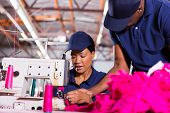 textile factory foreman helping young sewing machinist in clothing factory