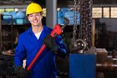 happy factory worker with monkey wrench in workshop