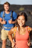 Hiking couple - Asian woman hiker walking on lava field on Hawaii. Tourists hikers on hike near Kila
