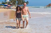 UNAWATUNA, SRI LANKA - MARCH 6, 2014: Tourist  couple walk on sandy beach. Unawatuna is a major tourist attraction in Sri Lanka  famous for its beautiful beach and corals.