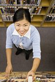 Asian woman taking library book off shelf