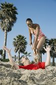 Mixed Race woman burying husband in sand