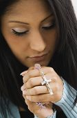 Hispanic woman holding rosary beads