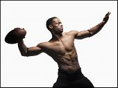 Bare chested football player throwing football