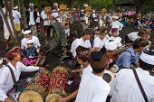 BALI, INDONESIA - SEPTEMBER 19, 2014: Traditional Balinese musical troupe plays music to accompany the prayer ceremonies for the Nyaben 12th day ceremony, to throw the cremated ashes into the sea.