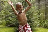 African American boy playing in sprinkler