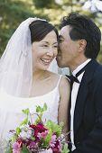Asian groom telling secret to bride