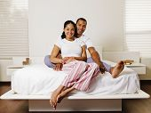 African couple sitting on bed