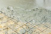 foto of concrete pouring  - Close up wire mesh and wet cement in concrete floor pouring process - JPG