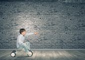 Little joyful cute boy riding tricycle in empty room