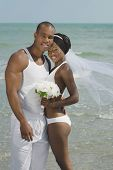 African bride and groom hugging at beach