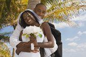 African bride and groom hugging