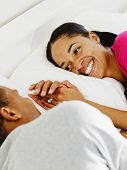 African couple smiling at each other in bed