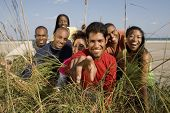 Multi-ethnic friends looking through grass