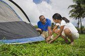 Multi-ethnic couple setting up tent