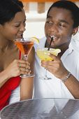 Multi-ethnic couple drinking cocktails