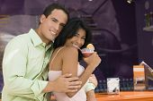 Hispanic couple hugging at bar