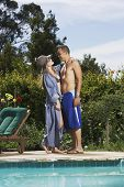 Multi-ethnic couple hugging next to swimming pool
