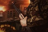 Soldier is holding gun on apocalyptic background