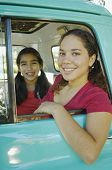 Hispanic mother and daughter sitting in truck