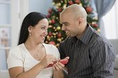 Hispanic woman opening Christmas gift from husband