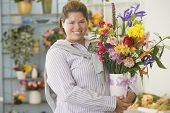 Hispanic woman holding flowers in vase