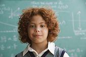 Mixed Race boy standing in front of blackboard