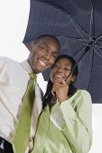 Hispanic couple standing under umbrella