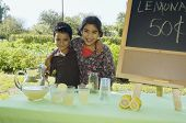 stock photo of pre-adolescents  - Hispanic siblings selling lemonade - JPG