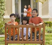Asian siblings sitting in bench